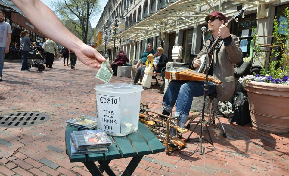 Eric Royer, of the South End, who performs as Royer's One Man Band, performs outside Quincy Market, where the management company is seeking to impose new rules and fees on buskers who work the area.
